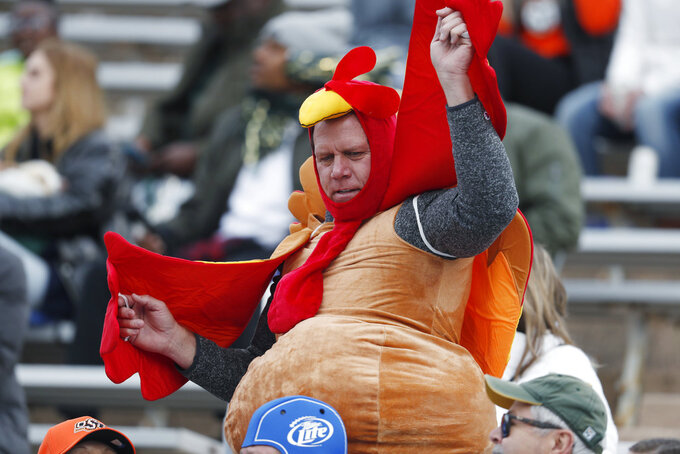 A fan dressed as a turkey dances in the stands in the first half of an NCAA college football game as Air Force hosts Colorado State Thursday, Nov. 22, 2018, at Air Force Academy, Colo. (AP Photo/David Zalubowski)