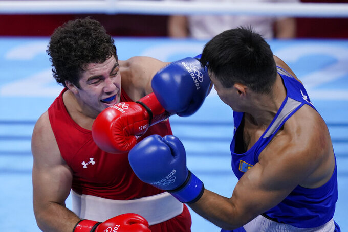 Richard Torrez Jr., of the United States, left, and Kamshybek Kunkabayev, of Kazakhstan, exchange punches during their super heavy weight +91kg semifinal boxing match at the 2020 Summer Olympics, Wednesday, Aug. 4, 2021, in Tokyo, Japan. (AP Photo/Frank Franklin II)