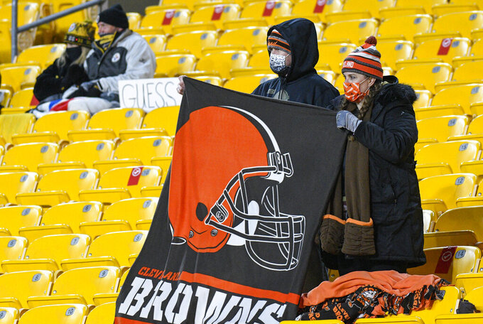 Cleveland Browns fans stand during the second half of an NFL wild-card playoff football game against the Pittsburgh Steelers in Pittsburgh, Sunday, Jan. 10, 2021. (AP Photo/Don Wright)