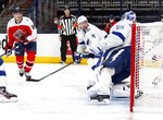 Columbus Blue Jackets forward Jack Roslovic, left, scores past Tampa Bay Lightning forward Tyler Johnson, center, and goalie Andrei Vasilevskiy during the second period of an NHL hockey game in Columbus, Ohio, Tuesday, April 6, 2021. (AP Photo/Paul Vernon)