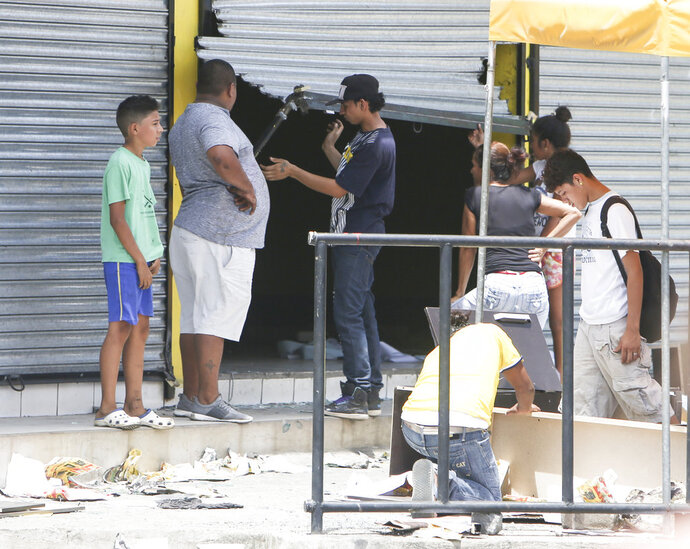 People stand in front of a store that has just been forced open and looted, in Managua, Nicaragua, Sunday, April 22, 2018. Dozens of shops in the Nicaraguan capital have been looted in the continuation of protests and disturbances sparked by government social security reforms. (AP Photo/Alfredo Zuniga)