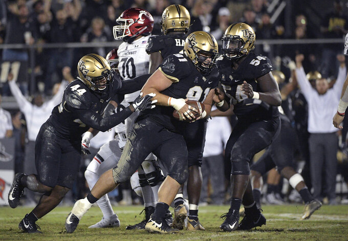 Central Florida defensive lineman Joey Connors (91) celebrates with linebacker Nate Evans (44) and defensive lineman A.J. Wooten (54) after recovering a fumble during the second half of an NCAA college football game against Cincinnati Saturday, Nov. 17, 2018, in Orlando, Fla. Central Florida won, 38-13. (AP Photo/Phelan M. Ebenhack)