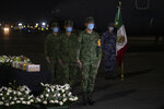 Mexican soldiers mourn five boxed cremated remains, of Mexicans who died from COVID-19, during a welcoming ceremony at the tarmac of Benito Suarez International airport in Mexico City, Saturday, July 11, 2020. The ashes of 245 Mexican were repatriated to Mexico from New York in a military airplane. (AP Photo/Fernando Llano)