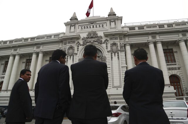 FILE - In this Sept. 30, 2019 file photo, security officers stand outside Congress where lawmakers are expected to push forward a vote to select an almost-full slate of new magistrates to the Constitutional Tribunal, in Lima, Peru. Peru's Constitutional Court has backed President Martín Vizcarra's controversial decision to dissolve the nation's legislature in 2019, with magistrates voting on Jan. 14, 2020 to ratify Vizcarra's move and dismiss a complaint backed by opposition lawmakers. (AP Photo/Martin Mejia, File)