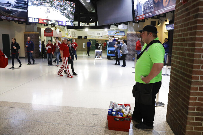 A concession worker waits in the lobby during the second half of an NCAA college basketball game between Northwestern and Minnesota at the Big Ten Conference tournament, Wednesday, March 11, 2020, in Indianapolis. Minnesota won 74-57. (AP Photo/Darron Cummings)