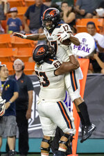 Oregon State offensive lineman Gus Lavaka (63) lifts his teammate wide receiver Isaiah Hodgins (17) after Hodgins catches a pass for a touchdown during the first half of an NCAA college football game against Hawaii, Saturday, Sept. 7, 2019, in Honolulu. (AP Photo/Eugene Tanner)