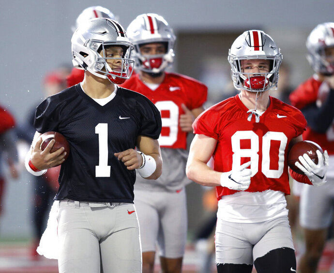 FILE - In this March 6, 2019, file photo, Ohio State quarterback Justin Fields, left, and wide receiver K.J. Hill run through a drill during the NCAA college football team's practice in Columbus, Ohio. First-year coach Ryan Day of defending conference champion Ohio State insisted after the Buckeyes' spring game last Saturday he hadn't decided between Georgia transfer Justin Fields and redshirt freshman Matthew Baldwin, who spent much of last season rehabbing a knee injury. Baldwin announced he would transfer on Thursday, April 18, 2019, erasing any doubt that Fields, the biggest acquisition of the offseason, would be the starter. (AP Photo/Paul Vernon, File)