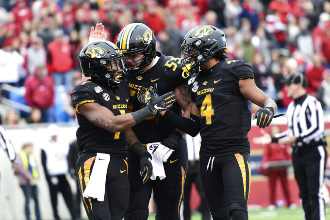 Missouri receiver Tyler Badie (1) celebrates with Trystan Colon-Castillo (55) and Jonathan Nance (4) after scoring a touchdown against Arkansas during the second half of an NCAA college football game Friday, Nov. 29, 2019 in Little Rock, Ark. (AP Photo/Michael Woods)