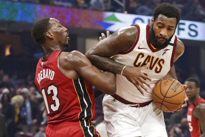 FILE - Cleveland Cavaliers' Andre Drummond, right, drives past Miami Heat's Bam Adebayo in the first half of an NBA basketball game, in Cleveland. Cavaliers center Andre Drummond said he'll exercise his $28.7 million option for the 2020-21 season and stay with Cleveland. (AP Photo/Tony Dejak, File)