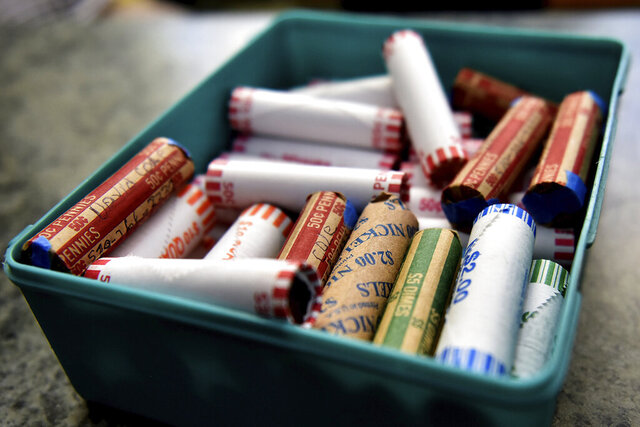 FILE - This Wednesday, July 15, 2020 file photo shows rolls of coins in a container at a market in Nanticoke, Pa.  The Federal Reserve says the supply system for coins had been severely disrupted by the pandemic. While there were still enough coins out in the world, they aren't circulating as freely because businesses have been closed and consumers weren't spending as usual.   (Sean McKeag/The Citizens' Voice via AP)