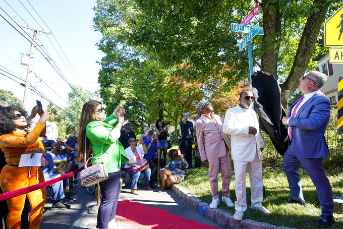 """Englewood Mayor Michael Wildes, right, unveils a street sign in honor of the Isley brothers as Ron Isley, center, and Ernie Isley look on during a street renaming ceremony, Thursday, June 24, 2021, in Englewood , N.J. Two New Jersey towns have renamed streets in honor of the Isley Brothers, the legendary R&B group that behind songs such as,  """"Shout,"""" """"Twist and Shout"""" and """"It's Your Thing."""" Ron Isley and Ernie Isley attended separate ceremonies Thursday in Teaneck and Englewood, neighboring towns outside New York City where they lived during the band's heyday in the 1960s. (AP Photo/Mary Altaffer)"""