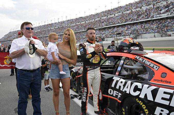 Austin Dillon stands next to his vehicle with his wife Whitney Dillon, their son, Ace, and car owner Richard Childress, left, on pit road before a NASCAR Cup Series auto race at Daytona International Speedway, Saturday, Aug. 28, 2021, in Daytona Beach, Fla. (AP Photo/Phelan M. Ebenhack)