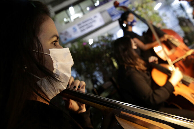 The Brasilia Philharmonic Orchestra performs at the HRAN Reference Hospital for COVID-19 in Brasilia, Brazil, Thursday, May 20, 2021. The concert is in honor of health professionals who work on the front lines to combat the pandemic. (AP Photo/Eraldo Peres)