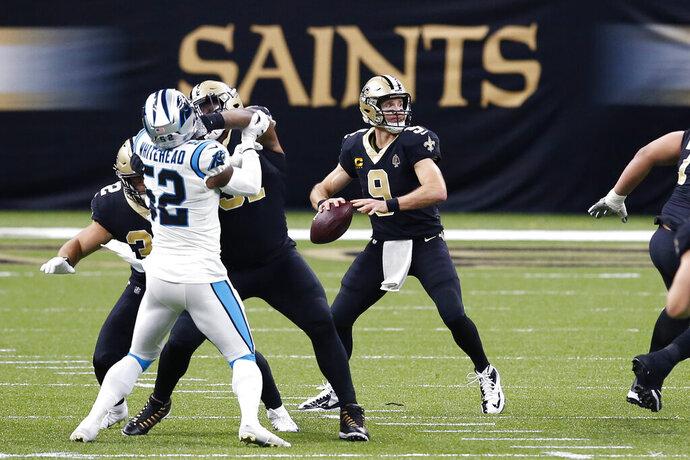 El quarterback Drew Brees (9), de los Saints de Nueva Orleans, lanza bajo presión en el duelo de la NFL ante los Panthers de Carolina, en Nueva Orleans, el domingo 25 de octubre de 2020. (AP Foto/Butch Dill)