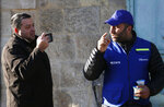 In this Tuesday, Feb. 12, 2019 photo, an Israeli settler, left, takes a picture of a Palestinian observer as he watches over children walking to school in the West Bank city of Hebron. Following Israel's expulsion of an international observer force from this volatile West Bank city, Palestinian activists are trying to fill the void by launching their own patrols to document alleged Israeli settler violence. (AP Photo/Majdi Mohammed)