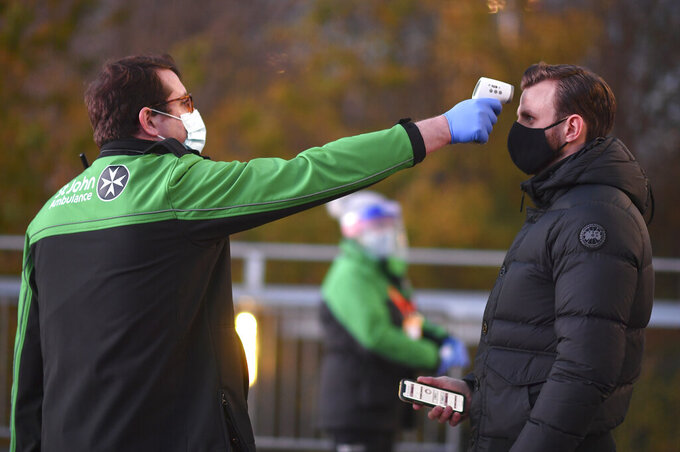 A West Ham United fan has their temperature taken before entering the stadium prior to the English Premier League soccer match between West Ham United and Manchester United at the London stadium in London, England, Saturday, Dec. 5, 2020. (Justin Setterfield/Pool Via AP)