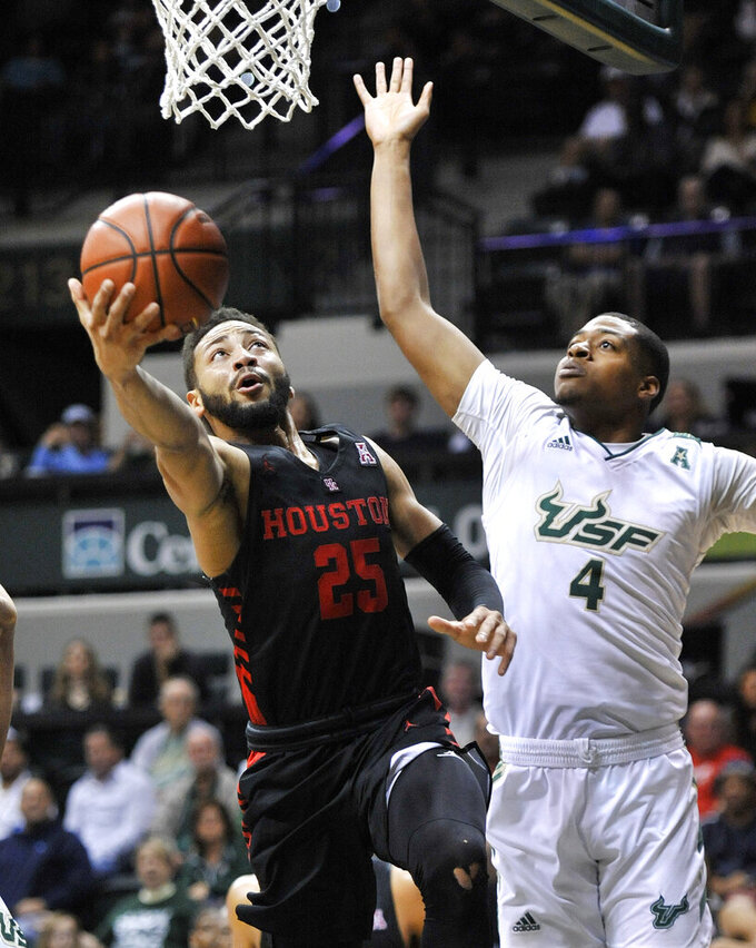 Houston's Galen Robinson Jr. (25) shoots under pressure from South Florida forward Michael Durr (4) during the second half of a NCAA college basketball game Saturday, Jan. 19, 2019 in Tampa, Fla. Houston defeated South Florida 69-60. (AP Photo/Steve Nesius)