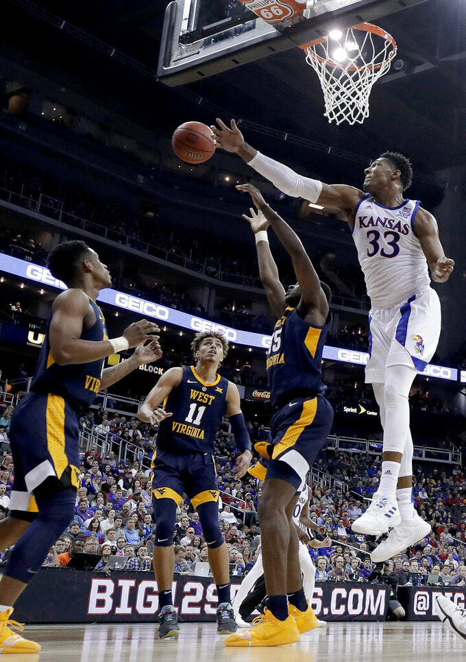 Kansas' David McCormack (33) bats away a rebound during the second half of the team's NCAA college basketball game against West Virginia in the Big 12 men's tournament Friday, March 15, 2019, in Kansas City, Mo. Kansas won 88-74. (AP Photo/Charlie Riedel)