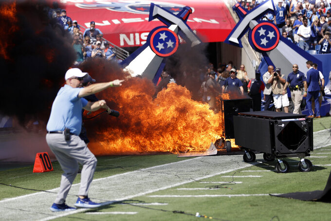 "FILE - In this Sunday, Sept. 15, 2019, file photo, a fire from a pyrotechnics machine burns on the field before an NFL football game between the Tennessee Titans and the Indianapolis Colts, in Nashville, Tenn. The NFL has banned any on-field pyrotechnics and ""flame effects"" at any league or team events, including games, in the wake of an incident at last Sunday's game at Nissan Stadium. (AP Photo/James Kenney, File)"