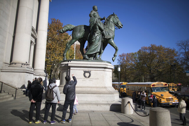 In this Nov. 17, 2017 file photo, visitors to the American Museum of Natural History in New York look at a statue of Theodore Roosevelt, flanked by a Native American man and African American man. The statue will be coming down after the museum's proposal to remove it was approved by the city (AP Photo/Mary Altaffer, File)