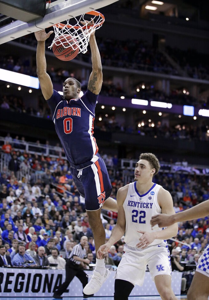 Auburn's Horace Spencer (0) dunks over Kentucky's Reid Travis (22) during the first half of the Midwest Regional final game in the NCAA men's college basketball tournament Sunday, March 31, 2019, in Kansas City, Mo. (AP Photo/Charlie Riedel)