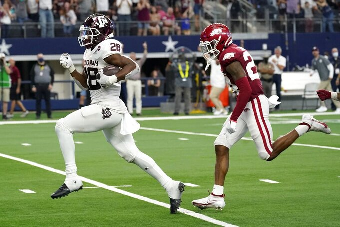Texas A&M running back Isaiah Spiller (28) sprints to the end zone for a touchdown after getting past Arkansas defensive back LaDarrius Bishop, right, in the second half of an NCAA college football game in Arlington, Texas, Saturday, Sept. 25, 2021. (AP Photo/Tony Gutierrez)