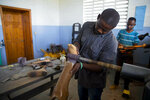In this May 8, 2019 photo, former welder Wilfrid Macena uses a grinding machine to repair a prosthetic limb at a workshop in the St. Vincent's Center, in Port-au-Prince, Haiti. In July 2010, he built his first prosthetic, a job that took him three days. Now, nine years and more than 3,000 prosthetics later, he's still at it, and it takes only four hours. (AP Photo/Dieu Nalio Chery)