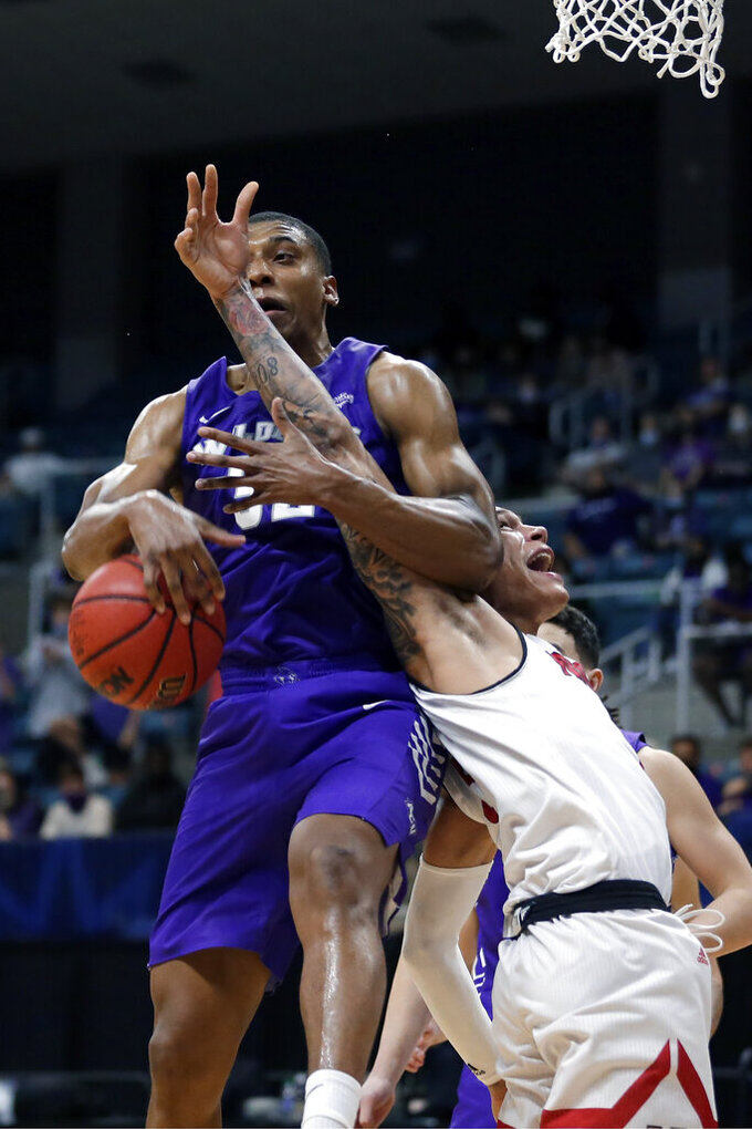 Abilene Christian forward Joe Pleasant, left, and Nicholls State forward Najee Garvin, right, go for a rebound during the second half of an NCAA college basketball game for the Southland Conference men's tournament championship Saturday, March 13, 2021, in Katy, Texas. (AP Photo/Michael Wyke)