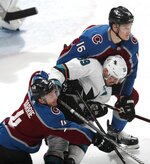 San Jose Sharks center Logan Couture, center, is sandwiched by Colorado Avalanche defensemen Tyson Barrie, bottom, and Nikita Zadorov during the third period of Game 4 of an NHL hockey second-round playoff series Thursday, May 2, 2019, in Denver. The Avalanche won 3-0. (AP Photo/David Zalubowski)