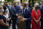 French President Emmanuel Macron hugs a child during a visit at Bouge primary school in Malpasse district of Marseille, southern France, Thursday Sept. 2, 2021 as twelve million children in France went back to school Thursday for the new academic year, wearing face masks as part of rules aimed at slowing down the spreading of the virus in the country. French President Emmanuel Macron, accompanied by several ministers, is on a three-day visit to the southern city of Marseille to address security, education and housing issues. (AP Photo/Daniel Cole, pool)