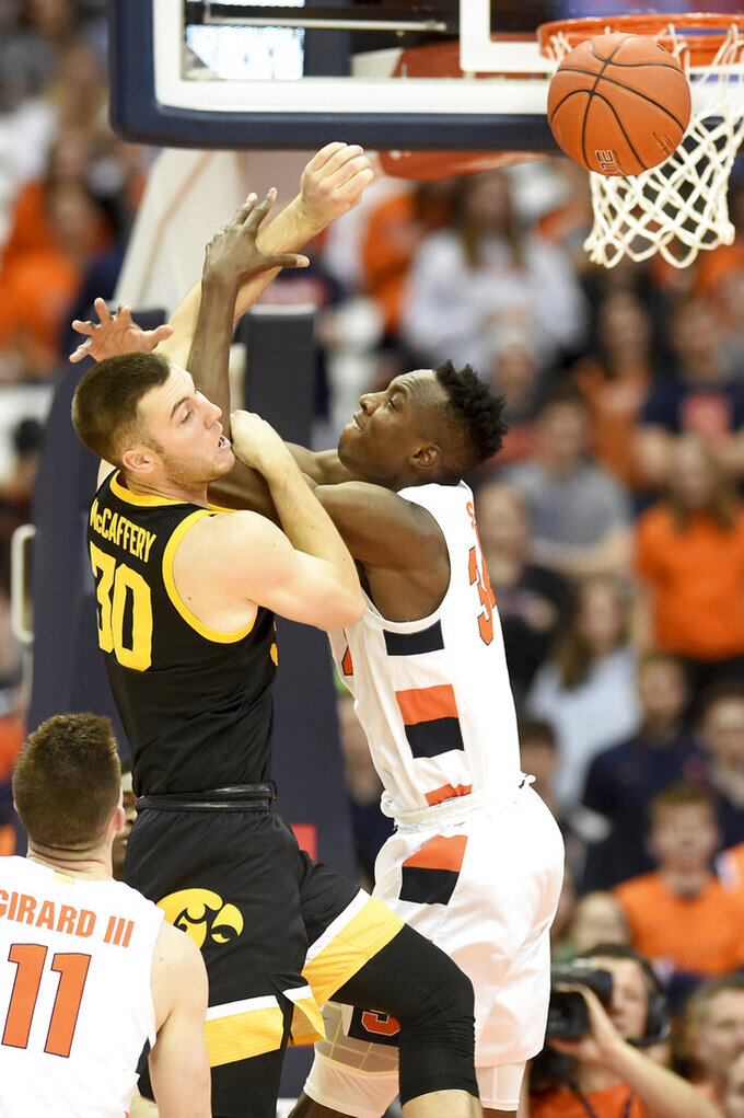 Iowa guard Connor McCaffery (30) and Syracuse center Bourama Sidibe (34) vie for a reboundd uring an NCAA college basketball game Tuesday, Dec. 3, 2019, in Syracuse, N.Y. (Dennis Nett/The Post-Standard via AP)