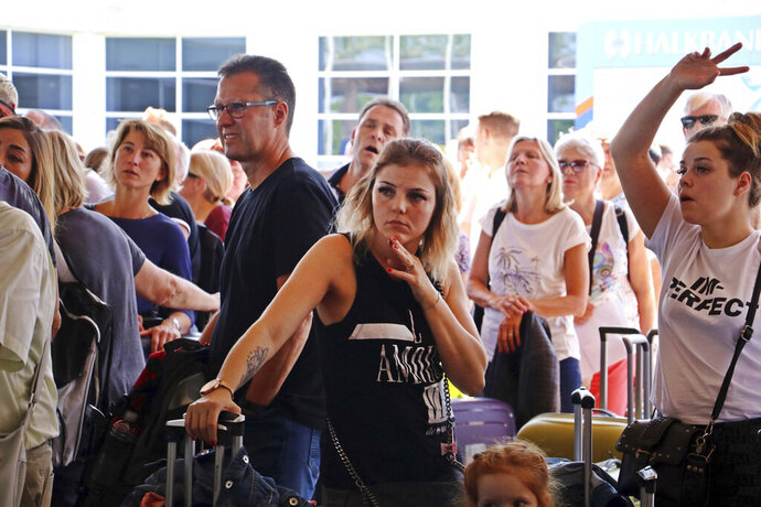 British passengers with Thomas Cook wait in queue at Antalya airport in Antalya, Turkey, Monday Sept. 23, 2019. Hundreds of thousands of travellers were stranded across the world Monday after British tour company Thomas Cook collapsed, immediately halting almost all its flights and hotel services and laying off all its employees. According to reports Monday morning some 21,000 Thomas Cook travellers were stranded in Turkey alone.(IHA via AP)