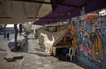 Palestinians walk next to covered vendors stalls in Gaza City, Tuesday, June 25, 2019, during a general strike against this week's economic conference in Bahrain that will kick off the Trump administration's plan for Mideast peace. (AP Photo/Khalil Hamra)