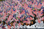 In this Saturday, Aug. 31, 2019, file photo, students wave national flags during 62nd Independence Day celebrations in Putrajaya, Malaysia. The Federation of Malaya gained its independence from Britain on Aug. 31 in 1957. (AP Photo/Vincent Thian, File)