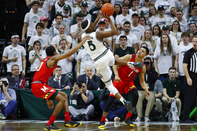 Michigan State guard Cassius Winston (5) shoots on Maryland guard Anthony Cowan Jr. (1) in the first half of an NCAA college basketball game in East Lansing, Mich., Saturday, Feb. 15, 2020. (AP Photo/Paul Sancya)