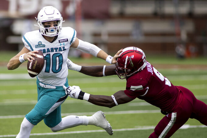 Troy defensive back Richard Jibunor (9) chases Coastal Carolina quarterback Grayson McCall (10) during an NCAA college football game, Saturday, Dec. 12, 2020, in Troy, Ala. (AP Photo/Vasha Hunt)