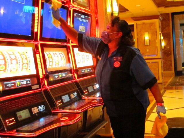 Jeorganna Barnes, a worker at Harrah's casino in Atlantic City, N.J., wipes slot machines with disinfectant Wednesday, July 1, 2020, as the casino prepared to reopen after 3 1/2 months of being shut down due to the coronavirus. Five of Atlantic City's casinos will reopen on Thursday, while three others, including Harrah's, will open Friday. (AP Photo/Wayne Parry)