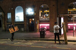 Furniture is cleared away outside a bar in Manchester's Northern Quarter as strict coronavirus restrictions on England's second-largest urban area, Greater Manchester, will start at midnight, Thursday, Oct. 22, 2020. (AP Photo/Jon Super)