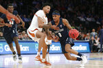 Texas forward Gerald Liddell (0) defends Georgetown guard James Akinjo (3) who drives to the basket during the second half of the first round of the 2K Empire Classic NCAA college basketball tournament, Thursday, Nov. 21, 2019, in New York. Georgetown defeated Texas 82-66. (AP Photo/Kathy Willens)