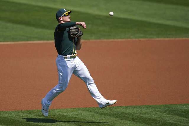 Oakland Athletics third baseman Matt Chapman makes a throwing error on San Diego Padres' Manny Machado's ground ball during the first inning of a baseball game in Oakland, Calif., Saturday, Sept. 5, 2020. (AP Photo/Jeff Chiu)