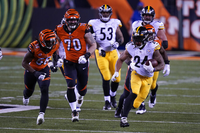 Pittsburgh Steelers' Benny Snell (24) is chased by Cincinnati Bengals' Carl Lawson (58) during the second half of an NFL football game, Monday, Dec. 21, 2020, in Cincinnati. (AP Photo/Bryan Woolston)