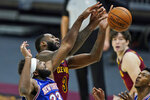 New York Knicks' Mitchell Robinson, left, and Cleveland Cavaliers' Andre Drummond reach for the ball during the second half of an NBA basketball game Friday, Jan. 15, 2021, in Cleveland. (AP Photo/Tony Dejak)