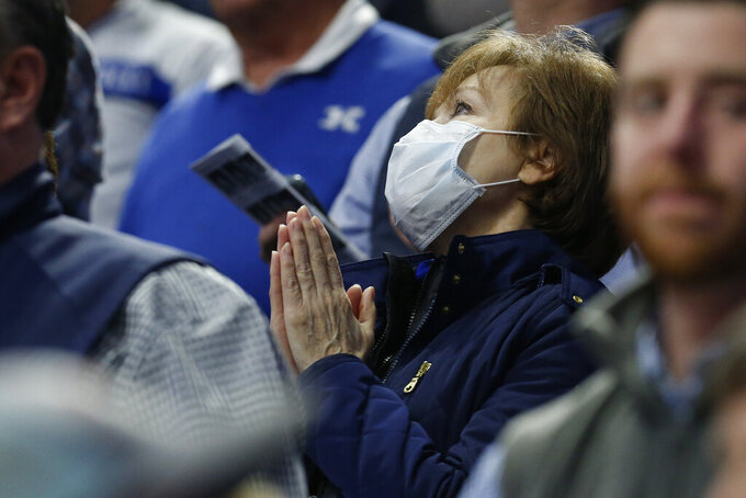 A Kentucky fan clasps her hands while wearing a mask late in the second half of Kentucky's NCAA college basketball game against Tennessee, Tuesday, March 3, 2020, in Lexington, Ky. Tennessee won 81-73. (AP Photo/James Crisp)