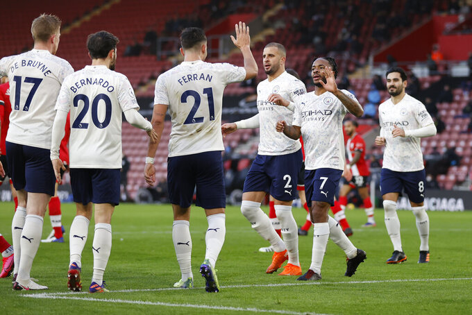 Manchester City's Raheem Sterling, second right, celebrates with teammates after scoring during the English Premier League soccer match between Southampton and Manchester City at the St Mary's Stadium, in Southampton, Saturday, Dec. 19, 2020. (Adrian Dennis/Pool via AP)