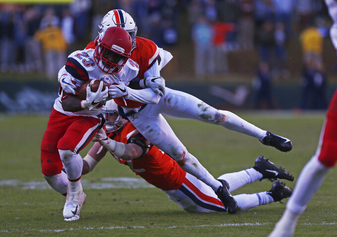 Liberty running back Frankie Hickson (23) is tackled by two Virginia defenders in the first half  of an NCAA college football game  Saturday, Nov. 10, 2018, in Charlottesville, Va. (Zack Wajsgras /The Daily Progress via AP)