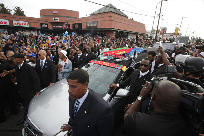 People watch as a hearse carrying the casket of slain rapper Nipsey Hussle passes Hussle's clothing store The Marathon, Thursday, April 11, 2019, in Los Angeles. Hussle's casket, draped in the flag of his father's native country, Eritrea in East Africa, embarked on a 25-mile tour of the city after his memorial service, drawing thousands to the streets to catch a glimpse of the recently-anointed hometown hero. (AP Photo/Jae C. Hong)