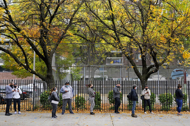 People wait in line at an early voting site in New York, Tuesday, Oct. 27, 2020. New Yorkers lined up to vote early for a fourth consecutive day Tuesday after a weekend that saw a crush of more than 400,000 voters statewide. The unofficial tally shows about 194,000 voters this weekend in New York City, where some people waited an hour or more in lines that stretched for several blocks. (AP Photo/Seth Wenig)