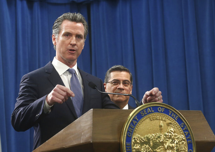 California Gov. Gavin Newsom, left, flanked by Attorney General Xavier Becerra, right, answers a question concerning a probable lawsuit the state will likely file against President Donald Trump over his emergency declaration to fund a wall on the U.S.-Mexico border Friday, Feb. 15, 2019, in Sacramento, Calif. Newsom and Becerra both say there is no emergency at the border and Trump doesn't have the authority to make the declaration. (AP Photo/Rich Pedroncelli)