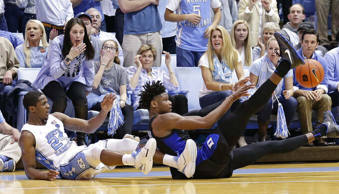 North Carolina's Kenny Williams (24) falls to the floor with Duke's Cam Reddish during the second half of an NCAA college basketball game in Chapel Hill, N.C., Saturday, March 9, 2019. North Carolina won 79-70. (AP Photo/Gerry Broome)