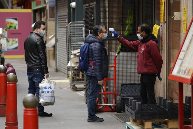 A customer has his temperature taken before entering the Loon Fung Chinese supermarket on Gerrard Street in London's Chinatown district, Sunday, May 3, 2020. The highly contagious COVID-19 coronavirus has impacted on nations around the globe, many imposing self isolation and exercising social distancing when people move from their homes. (AP Photo/Matt Dunham)